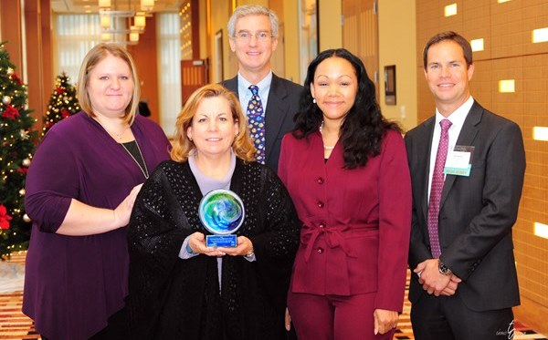 PRA employees accepted a Corporate Volunteer Excellence award on Dec. 4, 2013. Left to right: Stacy Gregory, senior operations manager; Lisa Lawson, internal auditor; Craig Grube, senior director, acquisitions; Diana Haynes, compliance analyst; and Chris Graves, executive vice president, core asset acquisitions.