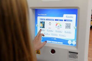 While shopping at the Alexandria, Va., Walmart location, Aleisha Butler, 24, takes a moment to utilize the SoloHealth Station, an interactive, self-service health care kiosk (Photo by Jack Gruber/USA Today).